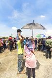 Woman held umbrella for her husband and son while watching aerobatic show at Bandung Air Show 2017. royalty free stock photography
