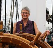 Woman at the Helm of a ship. Waman at the Helm of an old Sailing Ship stock photo