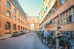 Woman in helmen on bicycle parking of historical swedish city. STOCKHOLM, SWEDEN - JUN 14, 2018: Woman in helmen on bicycle parking of historical swedish city on Stock Images