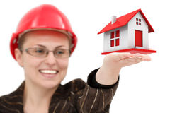 Woman in a helmet. An attractive young businesswoman with a safety helmet holding a house in her hand Stock Images