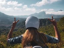 Woman in helmet admire beautiful mountain view in Bali. Back view of woman tourist in helmet admire beautiful view of Batur lake and Mount Agung in Bali royalty free stock photos