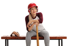 Woman with a helmet and a baseball bat sitting on a wooden bench Stock Photos