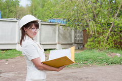 Woman in a helmet and by documents in hands Royalty Free Stock Images