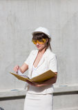 Woman in a helmet and by documents in hands Royalty Free Stock Photography