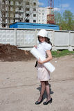 Woman in a helmet and by documents in hands on a backgrou Royalty Free Stock Images