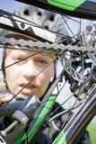 Woman in helmet repairing bicycle Stock Photos