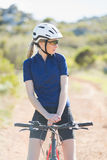 Woman with helmet sitting on bike and looking away Royalty Free Stock Images