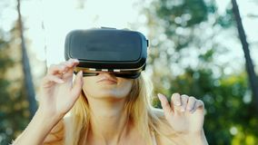 Woman in VR helmet. In the sun, beautiful lens flare. Woman in a helmet of virtual reality. In the sun, beautiful glare. Slow motion 4k video royalty free stock photos