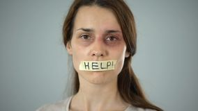 Woman with help sign on taped lips, helpless victim begging for support. Stock footage stock footage