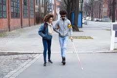 Woman Helping Blind Man While Crossing Road stock photos