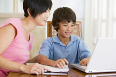 Woman helping boy with laptop doing homework stock photography