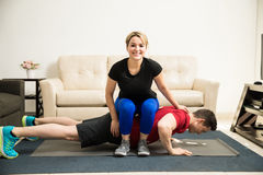 Woman helping boyfriend do some push ups Royalty Free Stock Images