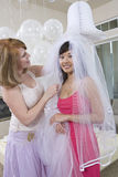 Woman Helping Bride In Dressing Up At Hen Party Stock Images