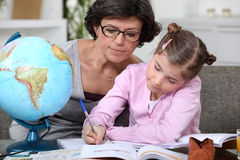 Woman helping a child with homework Royalty Free Stock Images