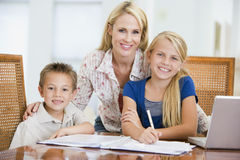 Woman helping children with laptop doing homework Royalty Free Stock Photography