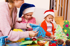 Woman helping  daughters  to make decoration for Xmas Stock Photo