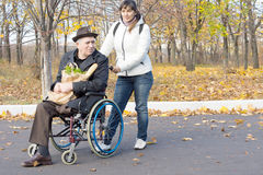 Woman helping a disabled pensioner in a wheelchair royalty free stock photography