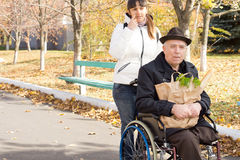Woman helping an elderly disabled man. Woman helping an elderly disabled men in a wheelchair by taking him out grocery shopping as they return together along the Stock Images