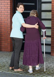 Woman helping elderly lady on crutches to enter house Stock Photos