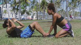 Woman helping exercising to man stock video
