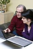 Woman helping father with laptop royalty free stock photography