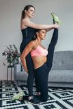 Woman helping friend in leg stretching workout at home.  Royalty Free Stock Photo