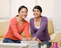 Woman helping friend wrap birthday gift stock photos