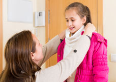 Woman helping girl to dress up Royalty Free Stock Photo