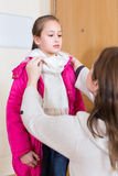 Woman helping girl to dress up Stock Photography
