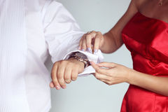 Woman helping the groom getting ready Royalty Free Stock Image