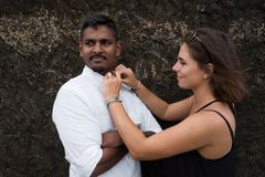 Woman helping her beloved man and fastening buttons on his shirt. Royalty Free Stock Images