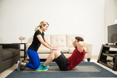 Woman helping her boyfriend exercise Stock Photo