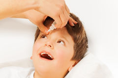 Woman helping kid boy to instill eye drops. Close-up portrait of woman helping to instill eye drops to five years old boy on blanked background Stock Images