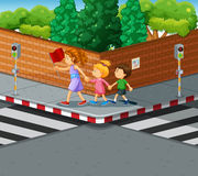 Woman helping kids crossing the street Stock Photo