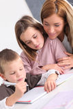 Woman helping kids with homework Royalty Free Stock Image