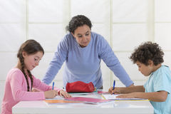 Woman helping kids with homework Stock Images