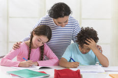 Woman helping kids with homework Stock Photo