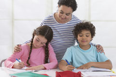 Woman helping kids with homework Stock Photos
