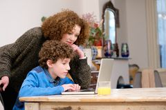 Woman helping little boy using computer at home Stock Photo