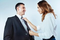 Woman helping man and adjusting tie over background. Wishing you good luck today. Side view on a successful business couple looking at each other while mindful Royalty Free Stock Images