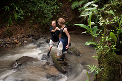 Woman helping man cross Costa Rican river Royalty Free Stock Photo