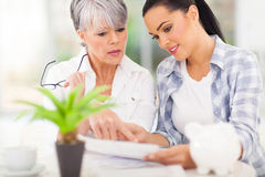Woman helping mother paying bills Royalty Free Stock Photo