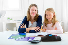 Woman helping out her little sister for homework Stock Photos