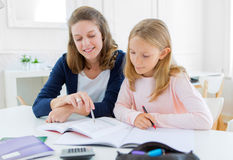 Woman helping out her little sister for homework Royalty Free Stock Image