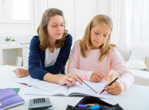 Woman helping out her little sister for homework Stock Photo