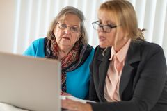Woman Helping Senior Adult Lady on Laptop Computer royalty free stock photo