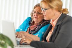 Woman Helping Senior Adult Lady on Laptop Computer royalty free stock photos
