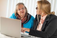 Woman Helping Senior Adult Lady on Laptop Computer stock photos