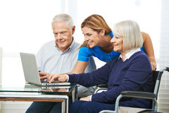 Woman helping senior couple with computer Stock Photos