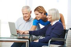 Woman helping senior couple with computer Stock Photos